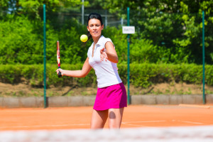Woman playing tennis on court outdoors with racket in her hand